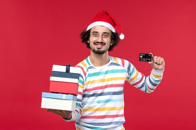Vista frontal jovem segurando presentes e cartão do banco na parede vermelha dinheiro de ano novo vermelho