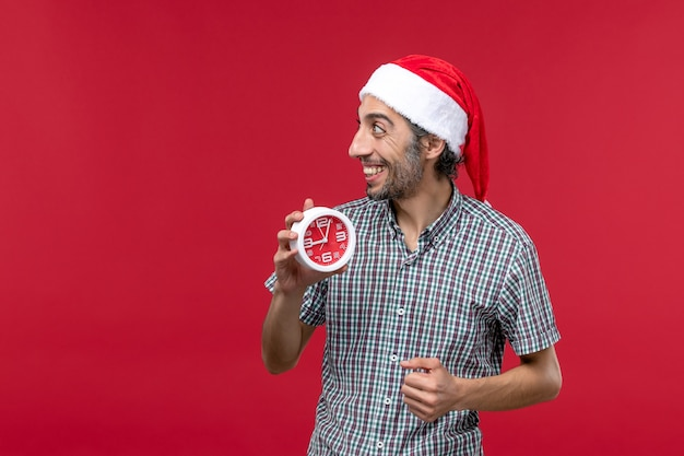 Vista frontal jovem segurando relógios na parede vermelha vermelha emoção tempo masculino