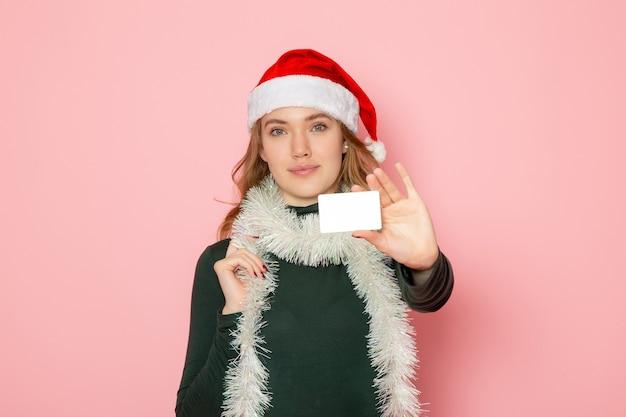 Vista frontal jovem segurando um cartão de banco branco com um leve sorriso na parede rosa cor emoção modelo férias natal ano novo