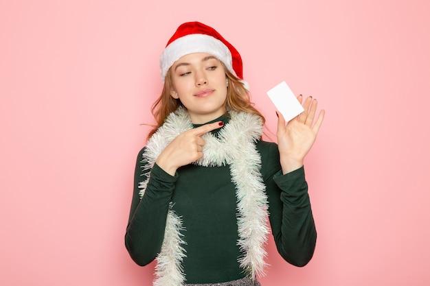 Vista frontal jovem segurando um cartão de banco branco na parede rosa cor emoção modelo férias natal ano novo