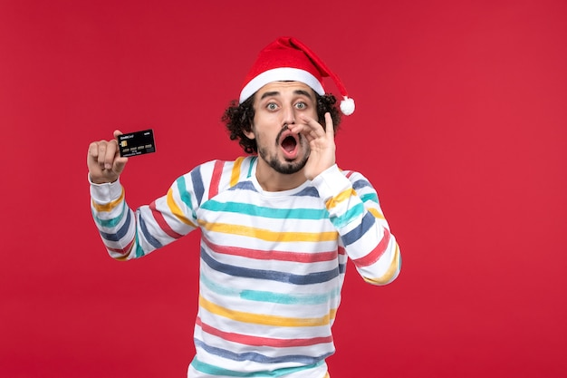 Vista frontal jovem segurando um cartão de banco preto na parede vermelha dinheiro vermelho masculino emoção férias