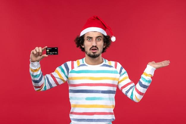 Vista frontal jovem segurando um cartão de banco preto na parede vermelha dinheiro vermelho masculino emoções férias
