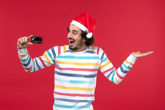 Vista frontal jovem segurando um cartão do banco na parede vermelha emoção vermelho masculino feriado