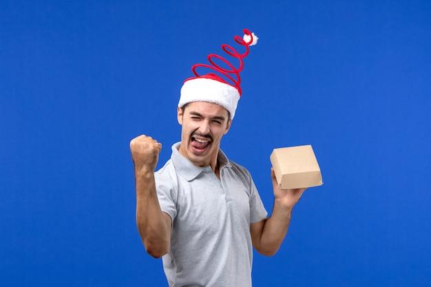 Vista frontal jovem segurando um pacote de comida na parede azul comida masculino serviço trabalho emoção
