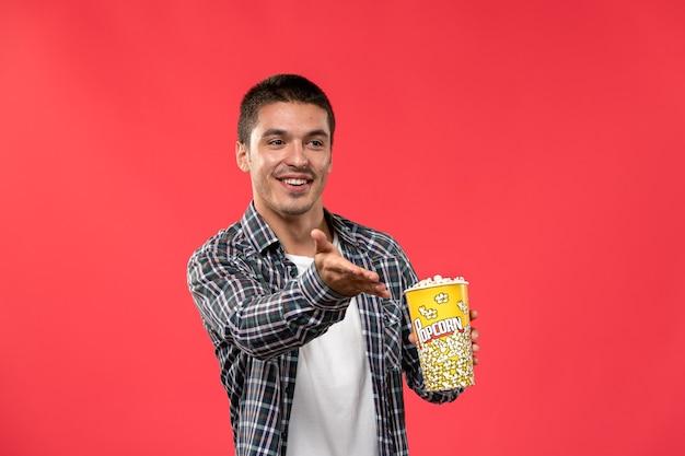 Vista frontal jovem segurando um pacote de pipoca na parede vermelha clara cinema teatro filme filme masculino
