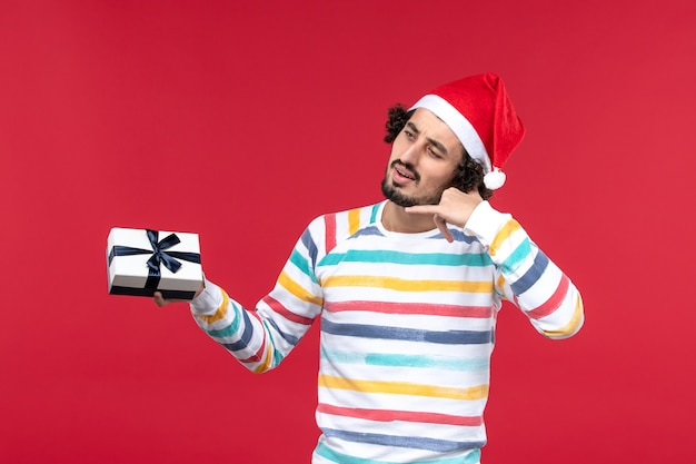 Vista frontal jovem segurando um presentinho na parede vermelha emoção feriado véspera de ano novo