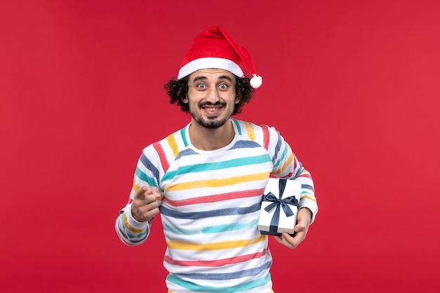 Vista frontal jovem segurando um presentinho no fundo vermelho emoção vermelha feriados ano novo