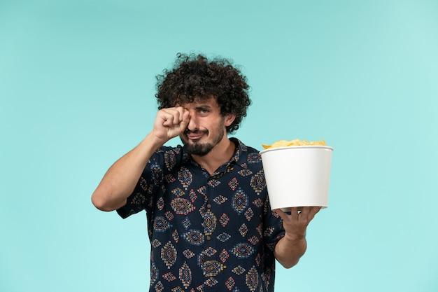 Vista frontal jovem segurando uma cesta com batata cips e assistindo filme chorando na parede azul cinema filme teatro masculino
