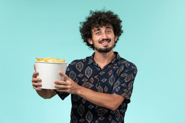 Vista frontal jovem segurando uma cesta com batata cips e assistindo filme na parede azul filme cinema filme remoto masculino