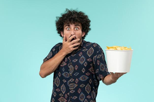 Vista frontal jovem segurando uma cesta com batatas cips e assistindo filme na mesa azul.
