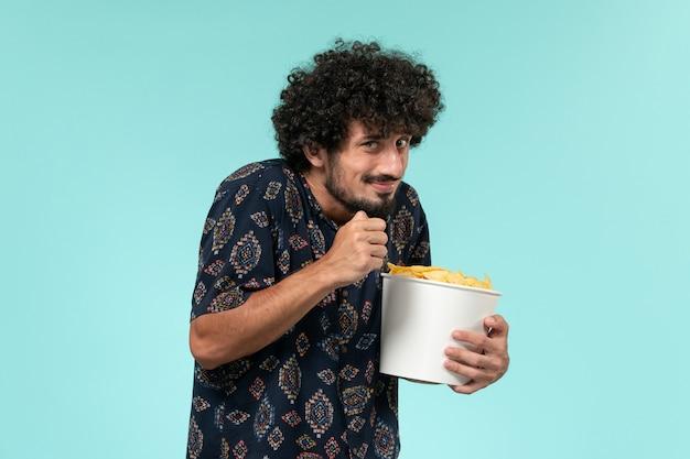 Vista frontal jovem segurando uma cesta com batatas cips e assistindo filme na parede azul cinema masculino cinema.