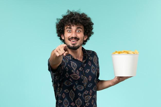 Vista frontal jovem segurando uma cesta com batatas cips e assistindo filme na parede azul.