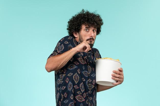 Vista frontal jovem segurando uma cesta com batatas cips e assistindo filme no cinema masculino de parede azul claro