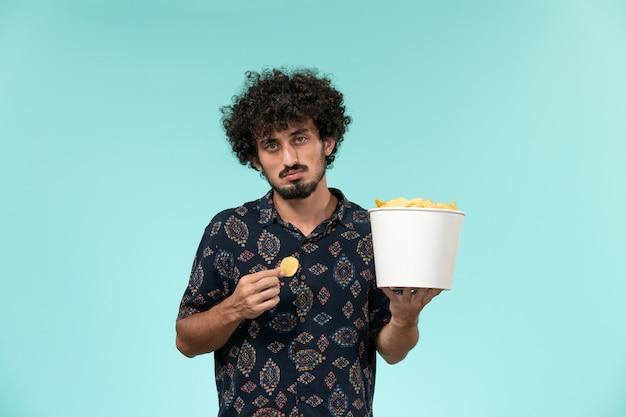 Vista frontal jovem segurando uma cesta com batatas cips e comendo na parede azul cinema filmes cinema teatro masculino