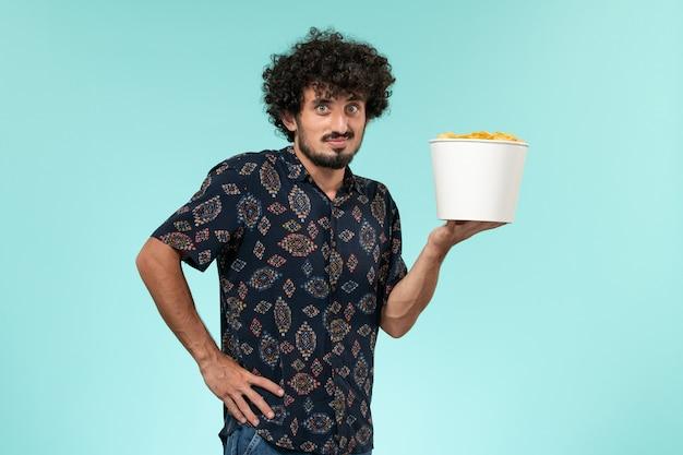 Vista frontal jovem segurando uma cesta com batatas cips na parede azul claro remoto filme cinema cinema teatro