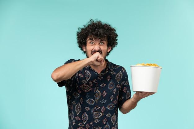 Vista frontal jovem segurando uma cesta com batatas fritas na mesa azul remoto filme cinema cinema teatro