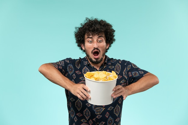 Vista frontal jovem segurando uma cesta com cips na parede azul filme remoto filme cinema