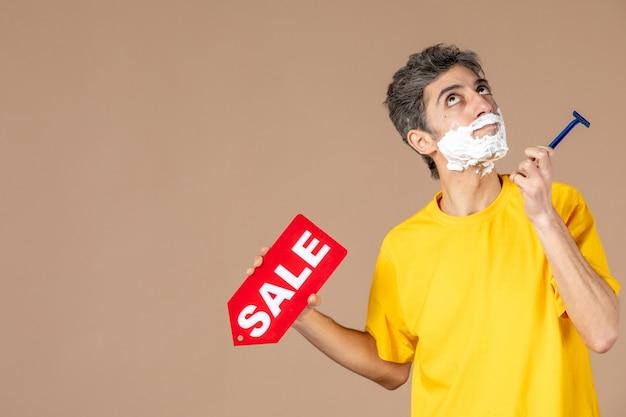 Vista frontal jovem segurando uma lâmina de barbear e placa de identificação de venda no fundo rosa