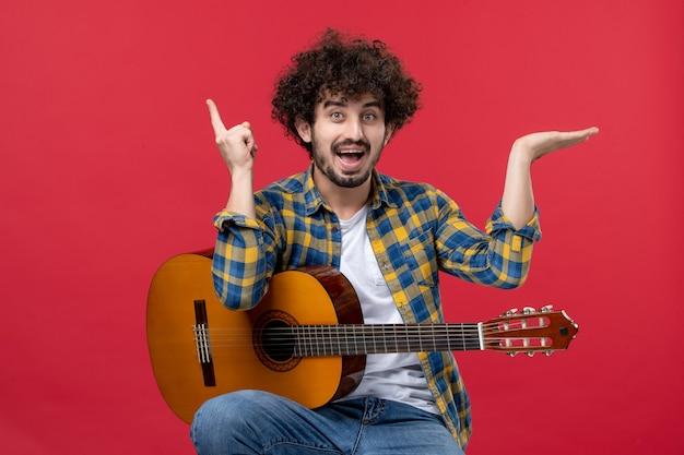 Vista frontal jovem sentado e tocando guitarra na parede vermelha concerto ao vivo cor músico aplauso música da banda