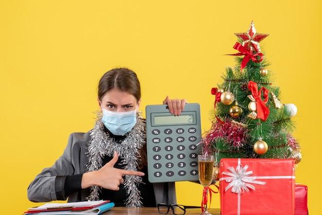 Vista frontal jovem séria com máscara médica sentada à mesa apontada com calculadora de dedo árvore de natal e coquetel de presentes
