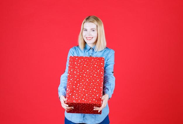 Vista frontal, jovem sorridente em pé no vermelho e quer dar uma caixa de presente para alguém