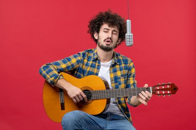 Vista frontal jovem tocando violão e cantando na cor vermelha do cantor da banda da banda, performance ao vivo do músico