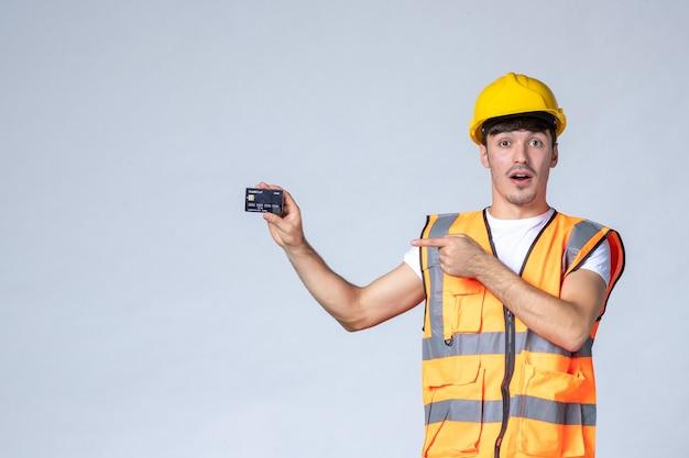 Vista frontal jovem trabalhador do sexo masculino com cartão do banco preto sobre fundo branco