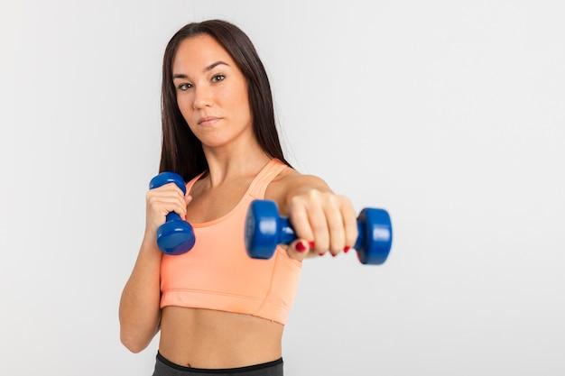 Vista frontal jovem treinamento feminino com pesos