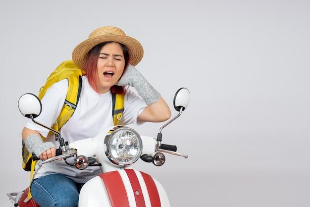 Vista frontal, jovem turista feminina sentada em uma motocicleta na parede branca velocidade mulher turista veículo foto passeio