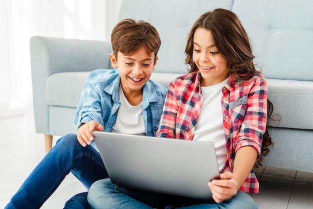 Vista frontal jovens irmãos com laptop