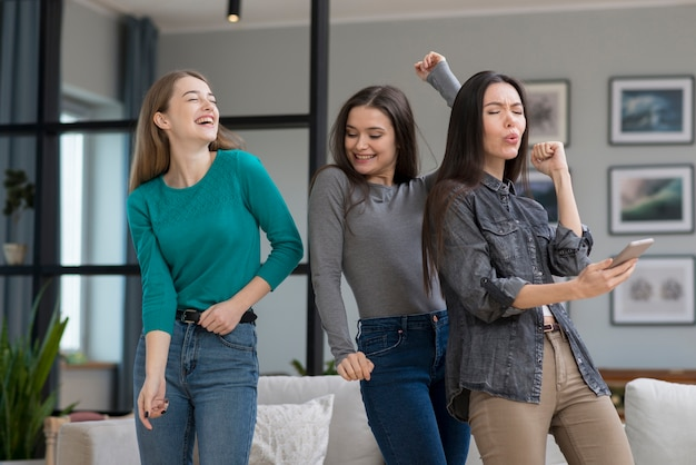 Vista frontal jovens mulheres dançando dentro de casa
