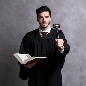Vista frontal juiz segurando o livro e martelo