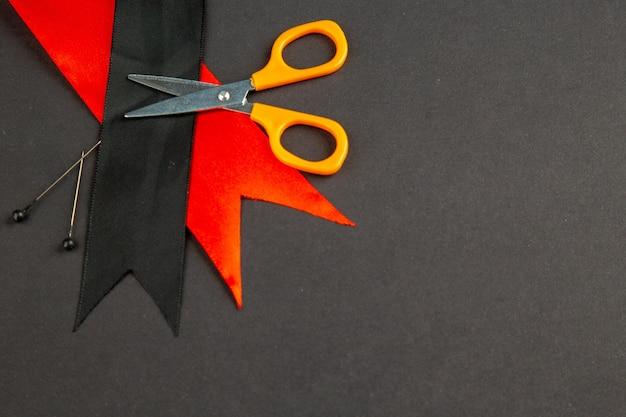 Vista frontal laço preto com laço vermelho e tesoura na superfície escura medida alfinetes de escuridão costura foto costurar roupas cores