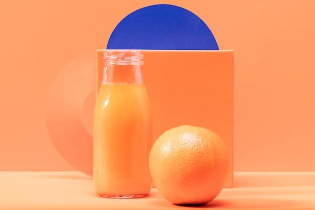 Vista frontal laranja e batido em frasco de vidro