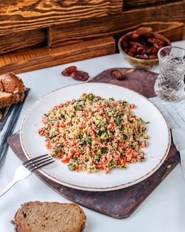 Vista frontal legumes cozidos picados colorido dentro de chapa branca na mesa de madeira marrom no chão marrom