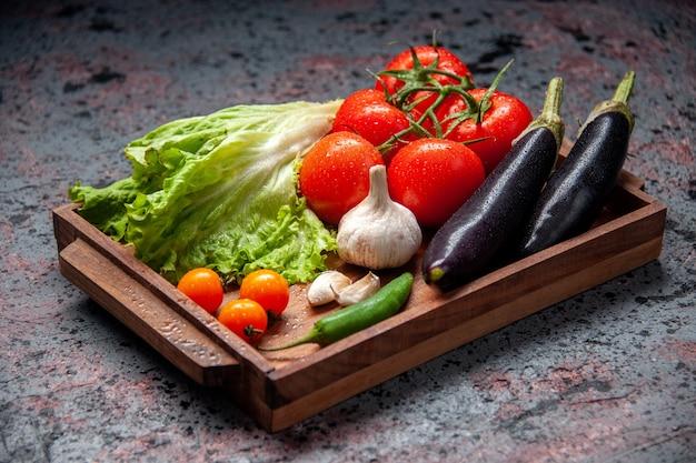 Vista frontal legumes frescos tomates vermelhos alho salada verde e berinjelas dentro de uma placa de madeira sobre fundo azul
