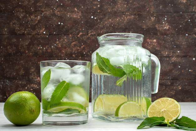Vista frontal, limão azedo fresco dentro e fora da lata de vidro com bebida de limão no suco tropical de frutas cítricas cinza