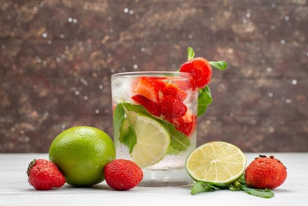 Vista frontal limão e morangos frescos e maduros com copo de água em branco, frutas baga bebida cítrica tropical