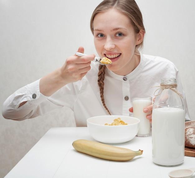 Vista frontal linda garota comendo cereais com leite