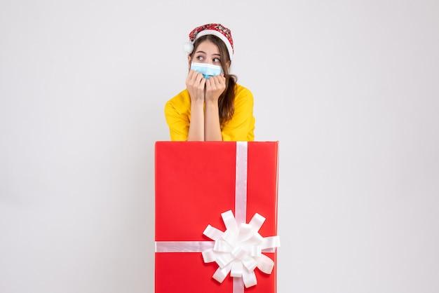 Vista frontal linda garota de natal com chapéu de papai noel atrás de um grande presente de natal