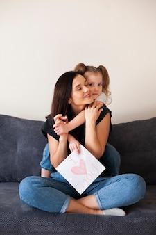 Vista frontal linda garota jovem abraçando sua mãe