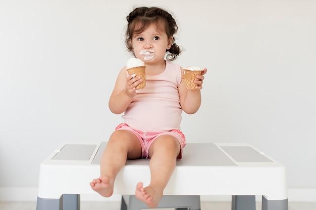 Vista frontal linda garota jovem tomando sorvete