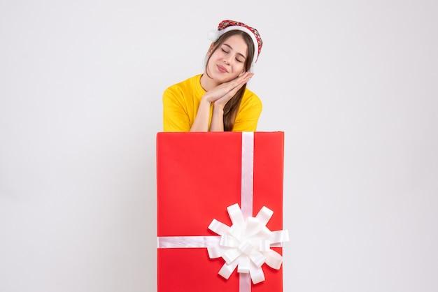 Vista frontal, linda garota sonolenta com chapéu de papai noel atrás de um grande presente de natal