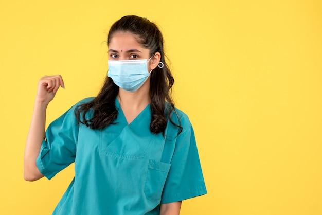 Vista frontal linda médica de uniforme apontando para trás em pé sobre fundo amarelo