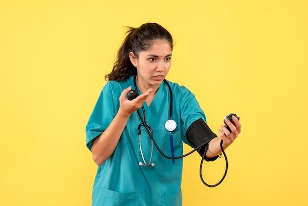 Vista frontal linda médica de uniforme verificando esfigmomanômetros em pé sobre fundo amarelo
