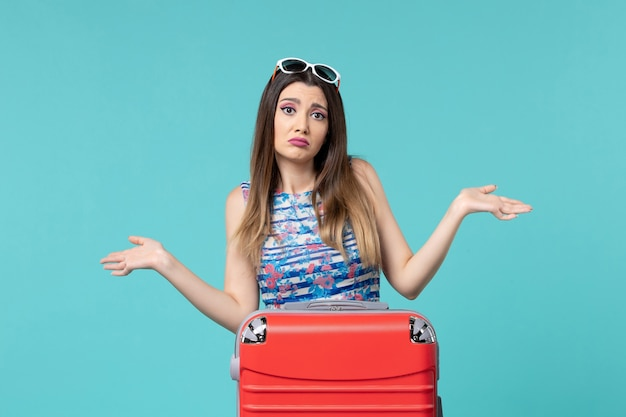 Vista frontal linda mulher se preparando para a viagem com sua grande bolsa vermelha na mesa azul