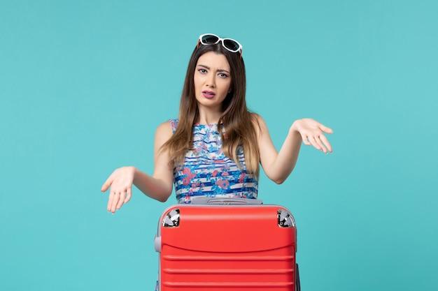 Vista frontal, linda mulher se preparando para a viagem com sua grande bolsa vermelha no espaço azul claro