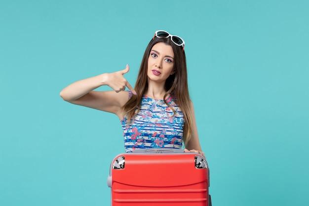 Vista frontal linda mulher se preparando para a viagem com sua grande bolsa vermelha no espaço azul