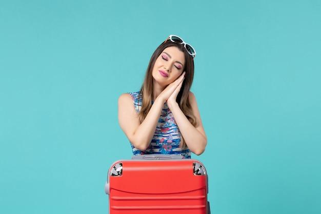 Vista frontal linda mulher se preparando para a viagem e se sentindo cansada no espaço azul