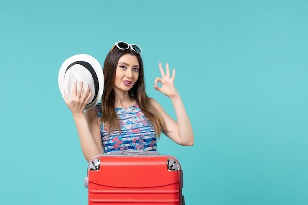 Vista frontal linda mulher se preparando para as férias com bolsa vermelha e chapéu no espaço azul